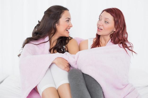 Amici femminili coperti a lenzuola mentre chiacchierano sul letto