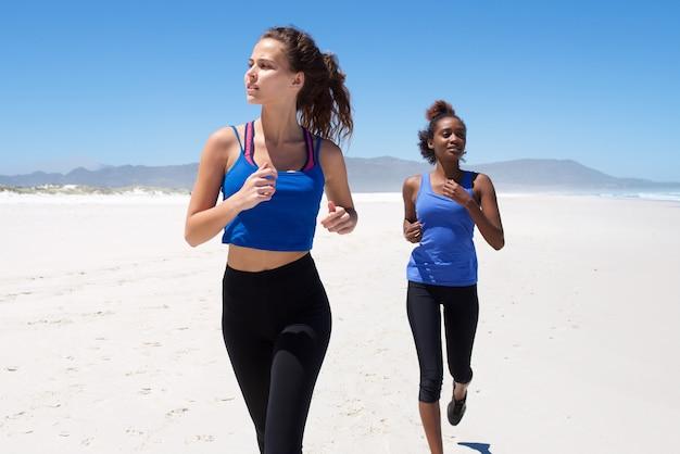 Amici femminili di forma fisica che pareggiano sulla spiaggia