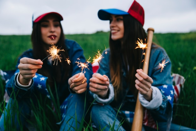 Amici femminili divertendosi con le luci del bengala