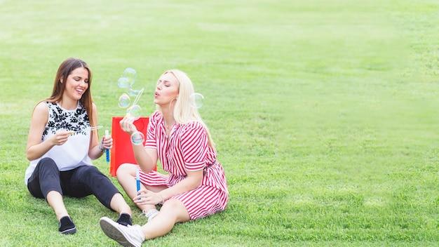 Amici femminili felici che godono del salto delle bolle nel parco