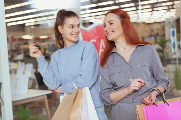 Amici femminili felici che ridono, godendo della compera insieme al centro commerciale
