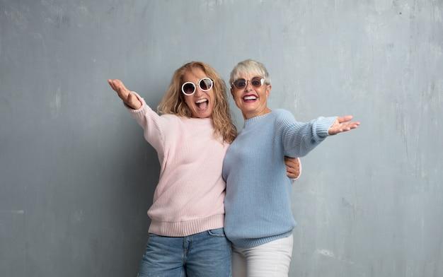 Amici femminili senior senior contro la parete del cemento di lerciume.