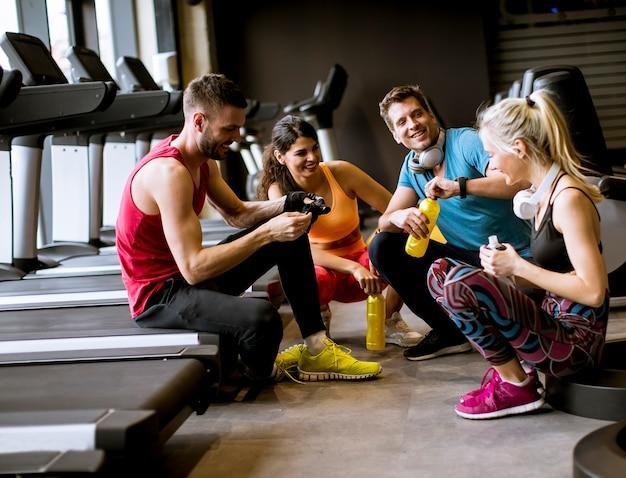 Amici in abiti sportivi a parlare e ridere insieme, seduti sul pavimento di una palestra dopo un allenamento