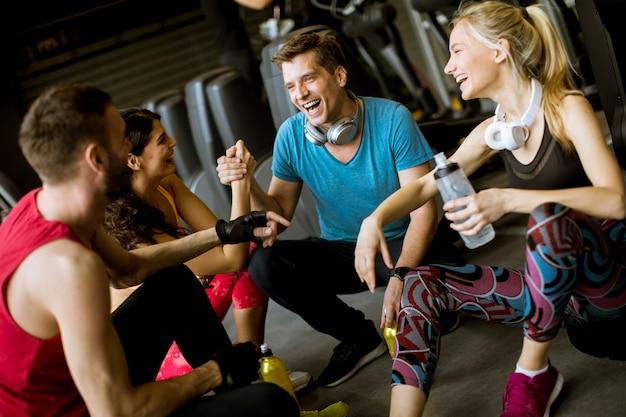Amici in abiti sportivi parlando e ridendo insieme mentre riposa in palestra dopo un allenamento