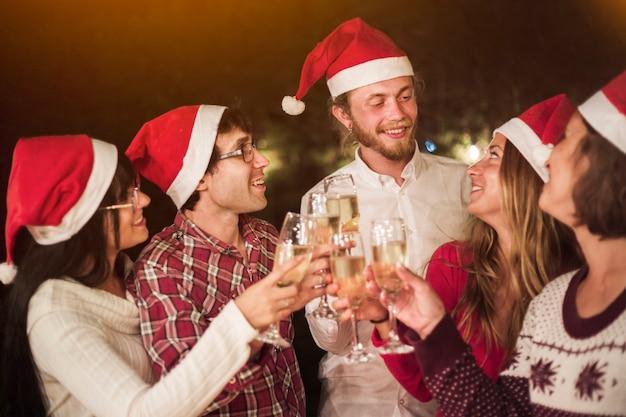 Amici in cappelli di santa tintinnio di bicchieri alla festa