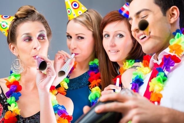 Amici in festa nel cocktail bar con cappelli e musica