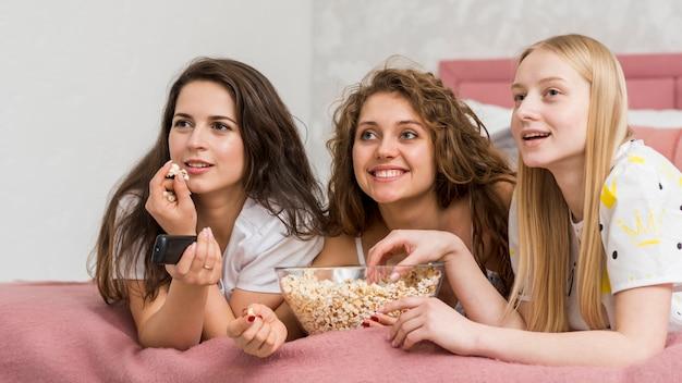 Amici in pigiama party a mangiare pop corn