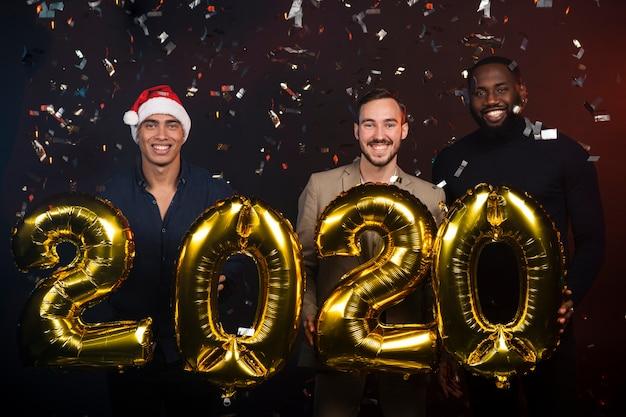 Amici in possesso di palloncini d'oro per i nuovi anni