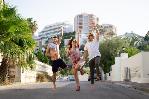 Amici in vacanza estiva, ridendo, divertendosi, saltando, camminando per le strade della città.