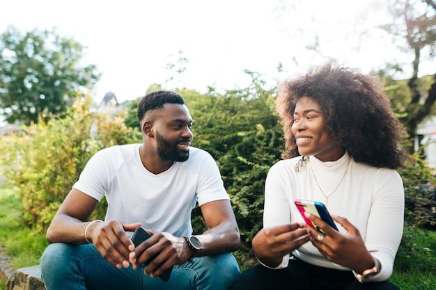 Amici interculturali di smiley che si siedono sul banco