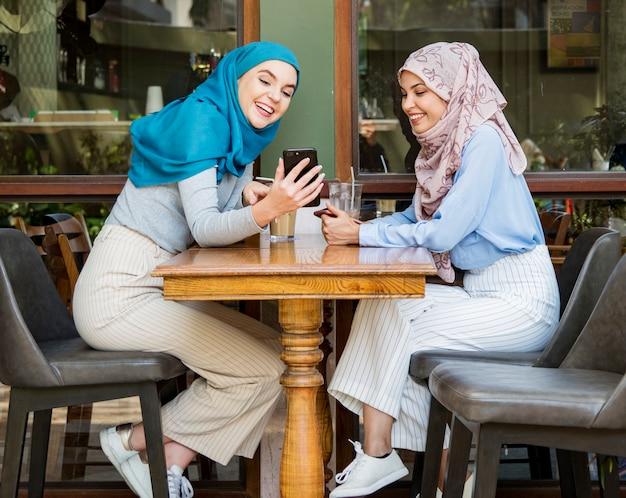 Amici islamici parlando e guardando sullo smart phone