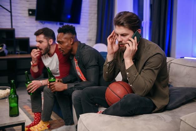 Amici maschi che guardano una partita e interferiscono con il loro amico maschio che parla al telefono