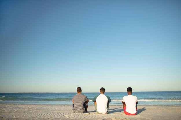 Amici maschi che si rilassano insieme sulla spiaggia