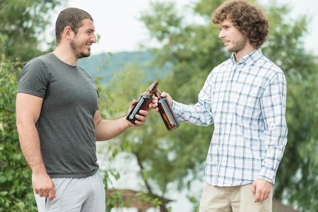 Amici maschii che clinking le bottiglie in natura