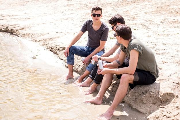 Amici maschii che godono dell'estate mentre sedendosi sulla spiaggia