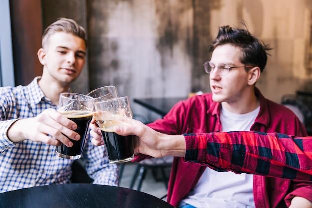 Amici maschii che tintinnano i bicchieri da birra sopra il tavolo