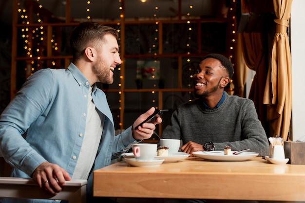 Amici maschii di angolo basso al ristorante