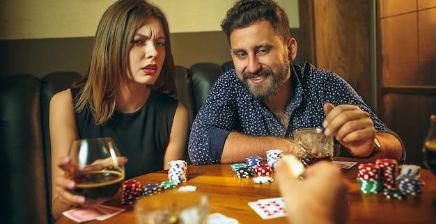 Amici maschii e femminili che si siedono alla tavola di legno. uomini e donne che giocano a carte. mani con il primo piano dell'alcool. poker, intrattenimento serale e concetto di eccitazione