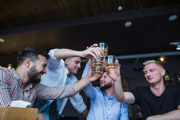 Amici maschii felici che tostano i vetri di whiskey