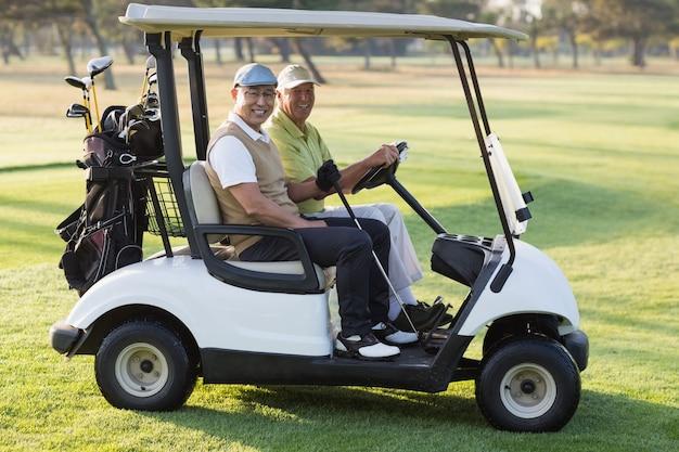 Amici maschii felici del giocatore di golf che si siedono in carrozzino di golf