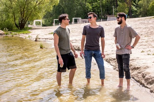 Amici maschii in occhiali da sole che stanno in riva vicina dell'acqua