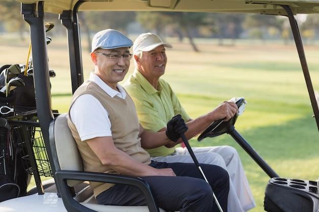 Amici maschii sorridenti del giocatore di golf che si siedono in carrozzino di golf