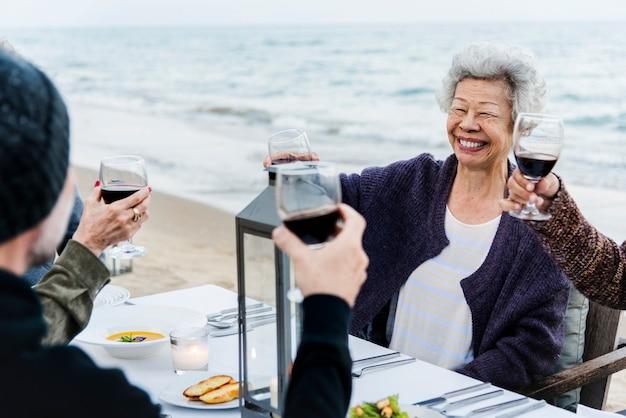 Amici maturi che bevono vino in spiaggia