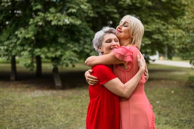 Amici maturi che si abbracciano