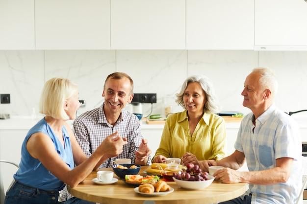 Amici maturi riuniti al tavolo della cucina