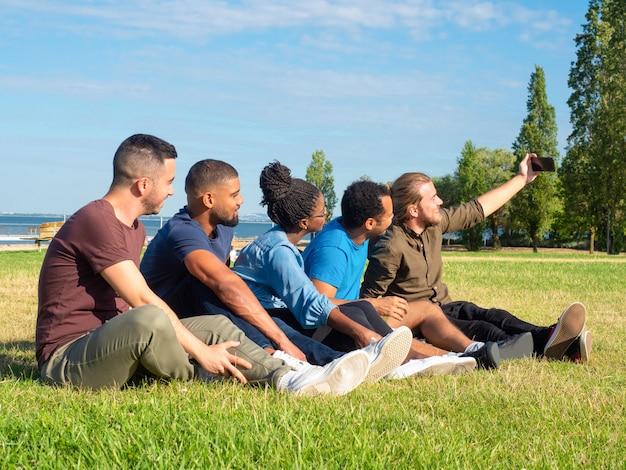Amici multietnici che prendono selfie in parco