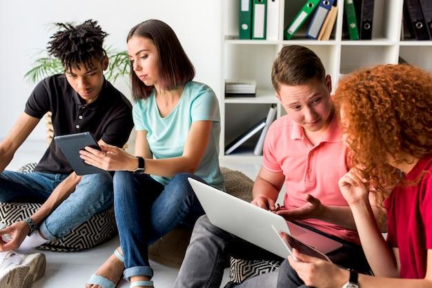 Amici multirazziali che utilizzano i dispositivi elettronici che si siedono sul pavimento che ha discussione