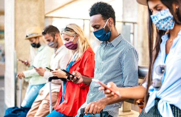 Amici multirazziali con maschera facciale utilizzando l'app di monitoraggio con smartphone mobile