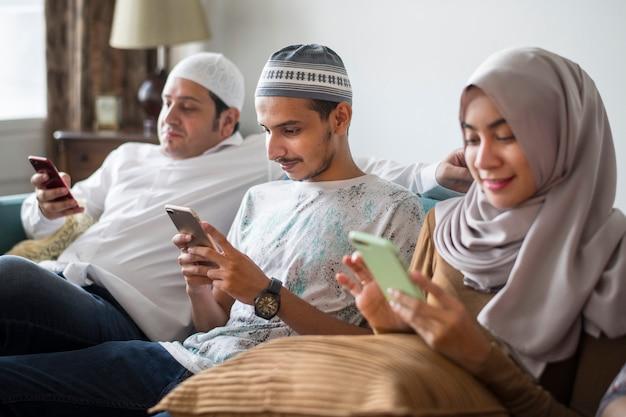 Amici musulmani che utilizzano i social media sui telefoni