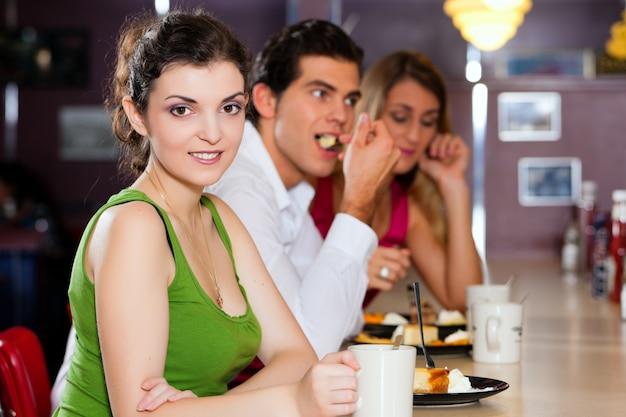 Amici nel ristorante a mangiare e bere