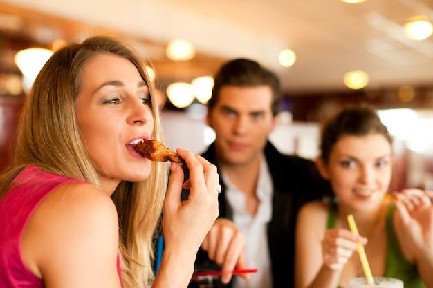Amici nel ristorante a mangiare fast food
