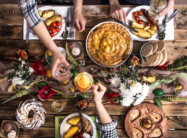 Amici o famiglia in vacanza a tavola festiva con carne di coniglio, verdure, torte, uova, vista dall'alto.