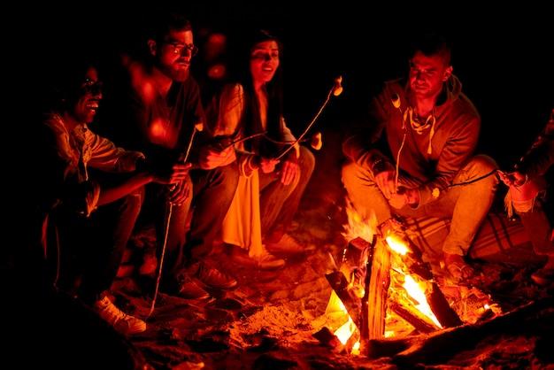 Amici positivi che arrostiscono le caramelle gommosa e molle su fuoco