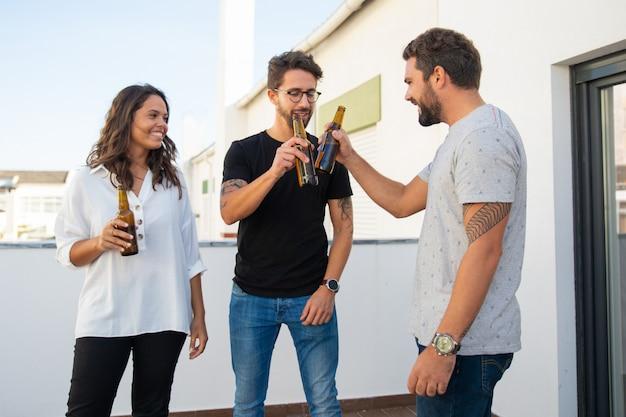 Amici positivi felici che celebrano e tostano la birra
