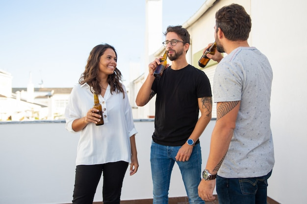 Amici positivi rilassati godendo la serata e bevendo birra