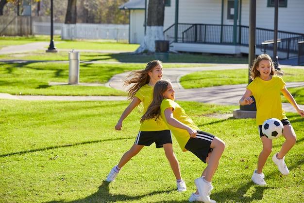 Amici ragazze adolescenti che giocano a calcio in un parco
