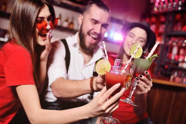 Amici-ragazzo giovane e due ragazze carine divertirsi a una festa in possesso di cocktail