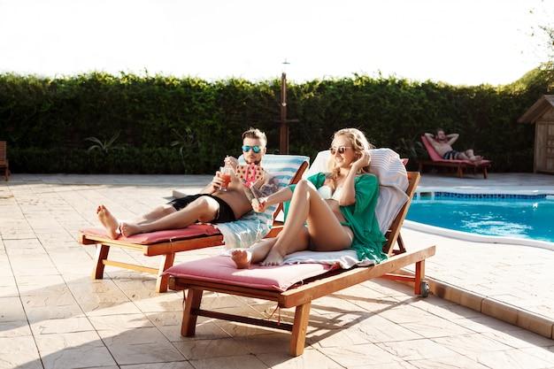 Amici sdraiati su sedie a sdraio vicino alla piscina, facendo selfie, sorridendo