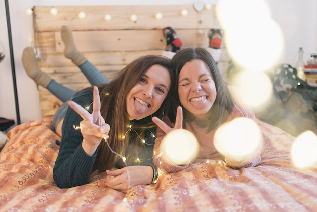 Amici sdraiati sul letto e sorridenti. concetto di amicizia