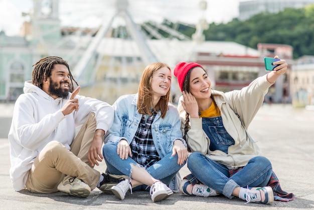Amici seduti sul pavimento e prendendo selfie