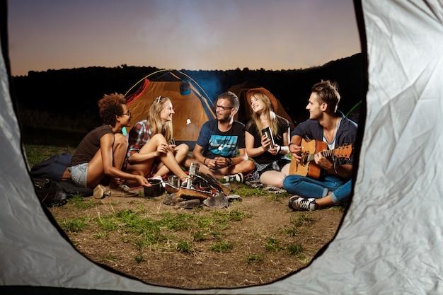 Amici seduti vicino al falò, sorridendo, suonando la chitarra campeggio marshmallow griglia.