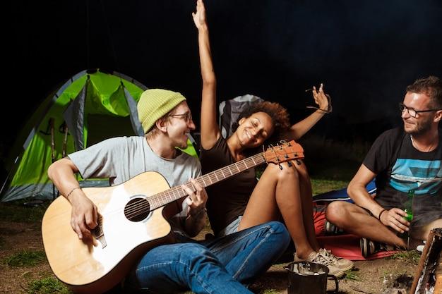 Amici seduti vicino al falò, sorridenti, parlando, riposando, suonando la chitarra