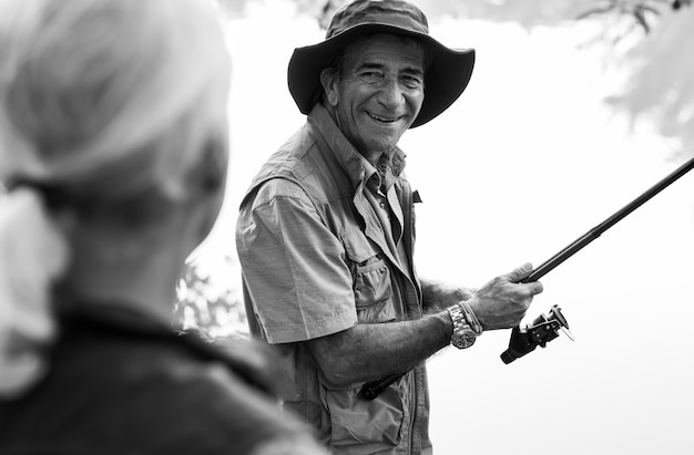 Amici senior che pescano in riva al lago