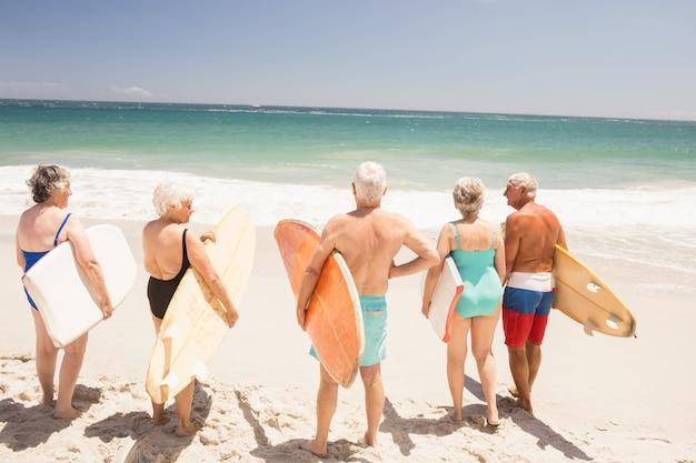 Amici senior che tengono tavola da surf