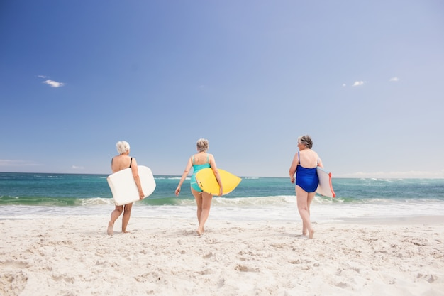 Amici senior della donna che tengono tavola da surf