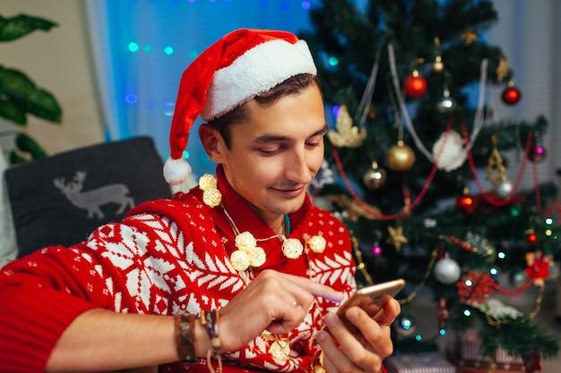 Amici sms uomo per natale utilizzando smartphone. guy festeggia il nuovo anno da solo a casa. operatore mobile